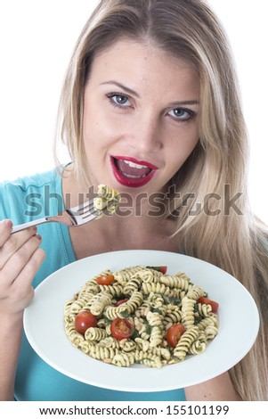 Model Released. Attractive Young Woman Eating Spinach and Pine Nut Pasta