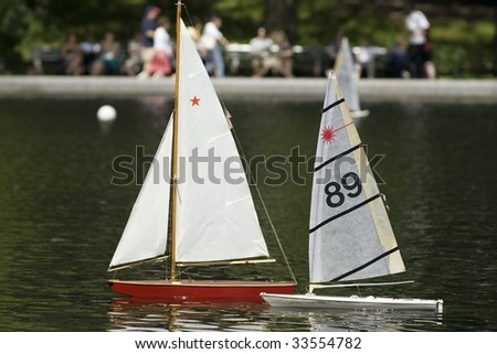 Model sailboats sailing by remote conctrol in a pool in Central Park New York City. - stock photo