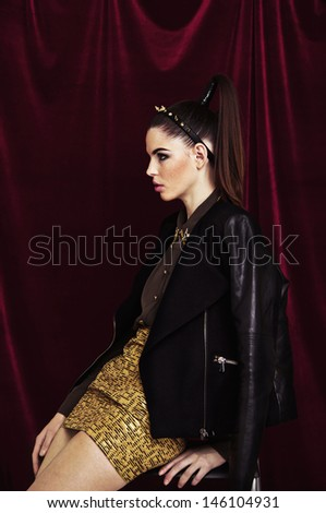 Model sitting in a half-turn, on a velvet background, She put the hoop on his head, and hair tied in a ponytail - stock photo