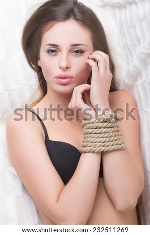 model tied up with fetish restraint rope. - stock photo