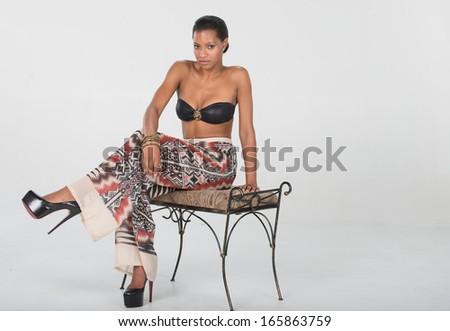 Model wearing beautiful mosiac print pants with black top. - stock photo