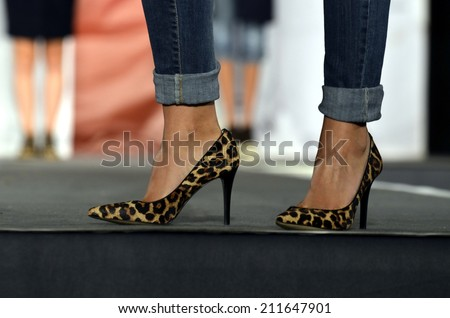 Model with a pair of fashion leopard female high heel shoes. Leopard pattern heeled shoe close-up on catwalk background - stock photo