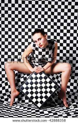 Model with body-art on the black and white square background and chessboard in hand - stock photo