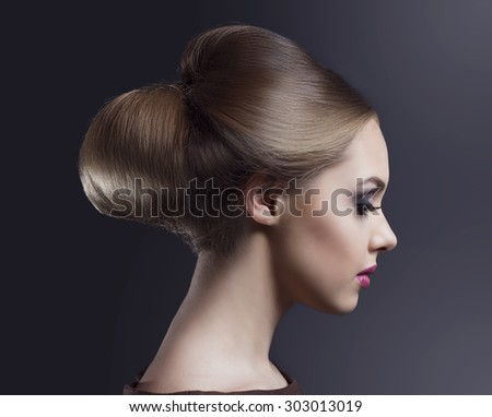 model with bright makeup and classic hairdo, against dark studio background