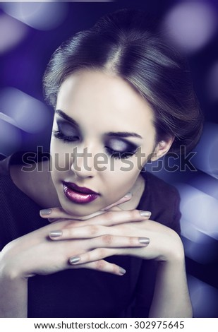 model with bright makeup and retro hair style, against dark studio background - stock photo