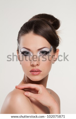 Model with creativity make-up with stylish hairstyle. Close-up portrait of young beautiful woman. - stock photo
