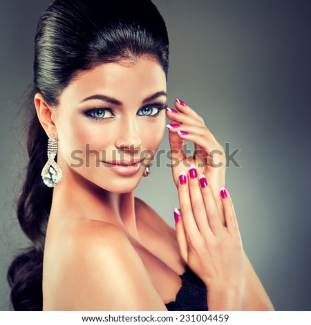 Model with long curly tail and fashionable earrings - stock photo