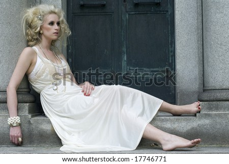 Model with no shoes leans against a gray column of an old building