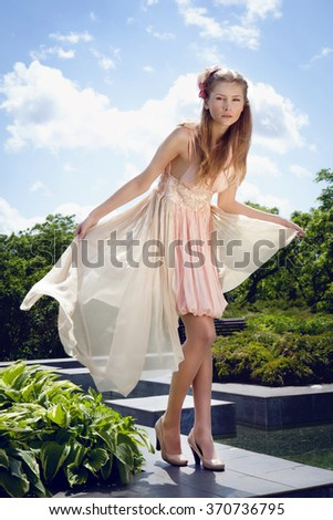 Model Woman wearing Long Chiffon dress. Beauty  girl  in blowing transparent chiffon dress.  Fashion woman  lady in summer park. Caucasian female model . outdoors . the wind blows dress - stock photo