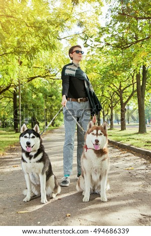 Model young girl with two dogs Husky walking through the park. Autumn landscape, warm weather.