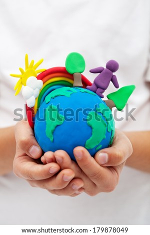Modelling clay earth with rainbow and trees in child hands - environment concept - stock photo