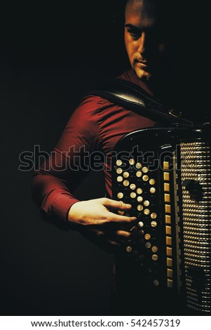 Modern accordion player posing with his chromatic harmonica type instrument.