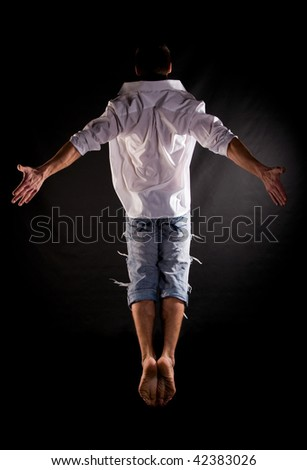 Modern acrobat jumping in front of black background - stock photo