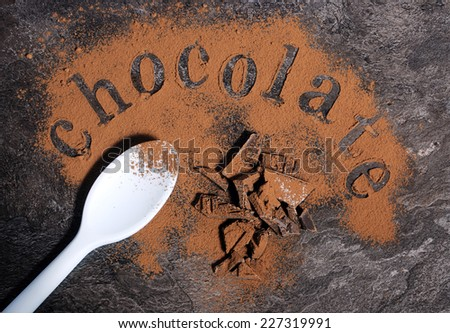 Modern aerial view of chocolate on black slate bench top table with pale blue spoon, spelling letters word with light chocolate dusting.