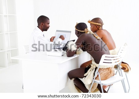 modern african businessman consulting with two traditional tribal clients - stock photo