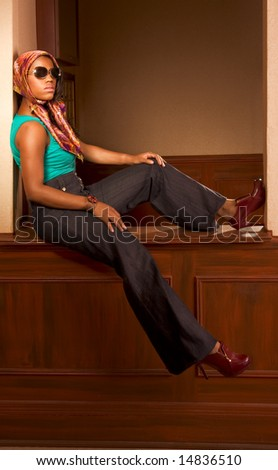 Modern Afro-American woman in jeans and sunglasses sitting table in lobby of apartment building