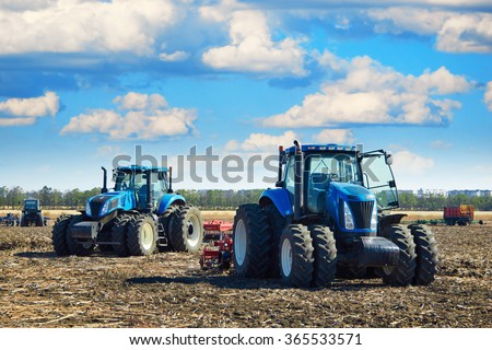 Modern agricultural machinery, tractors under a cloudy sky, agricultural machines, cultivation of the soil on the farm, a tractor working in a field, agricultural machinery in the work - stock photo
