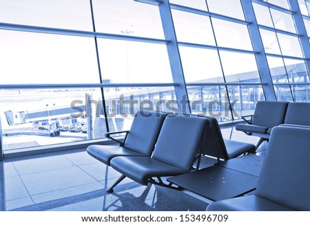 modern airport terminal waiting room with window outside scene of flight departure  - stock photo