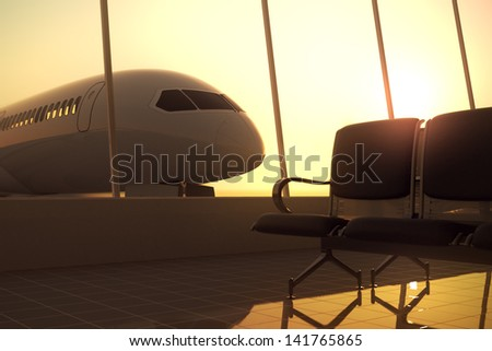 Modern airport terminal with black leather seats at sunset. A huge viewing glass facade with a passenger aircraft behind it. - stock photo