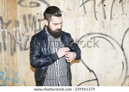 Modern and attractive man reaches into his pocket - stock photo