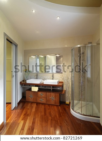 modern and luxurious bathroom with shower cubicle and wood floor - stock photo