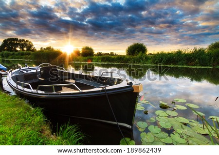 Modern and luxurious synthetic motor sloop in a river in the Netherlands at sunset - stock photo