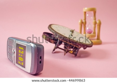 Modern and old fashioned clocks,  Low depth of field, focus on display of mobile phone - stock photo