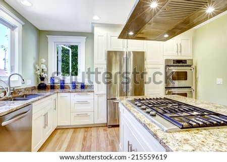 Modern and practical kitchen room design. White cabinet with granite tops and steel appliances, kitchen island with built-in stove and steel hood - stock photo