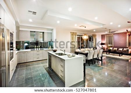 Modern and shiny kitchen with dining and living area including a counter top and kitchenware & Modern Shiny Kitchen Dining Living Area Stock Photo (Royalty Free ...