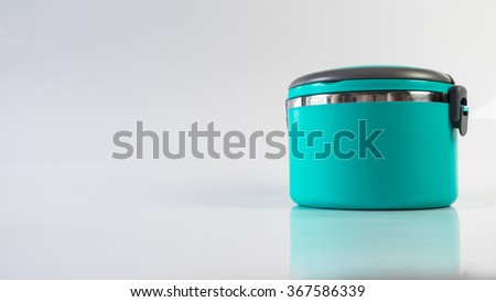 Modern and simplistic greenish blue color lunch box. Isolated on empty background. Slightly de-focused and close-up shot. Copy space.