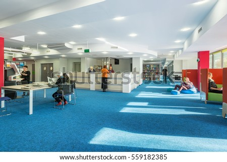 Modern And Spacious University Library With Blue Carpet On The Floor