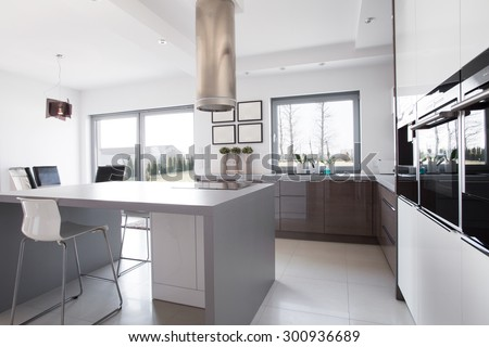 Modern and sunny kitchen with kitchen island in the middle - stock photo