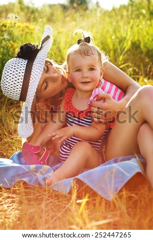Modern and young mother with a baby in nature - stock photo