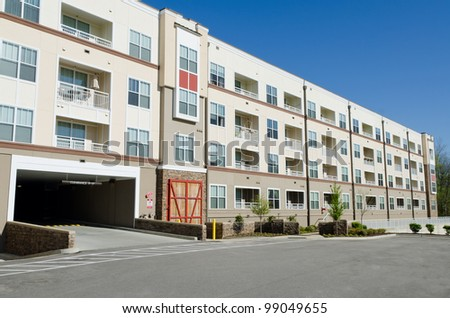 Modern apartment building with parking garage - stock photo
