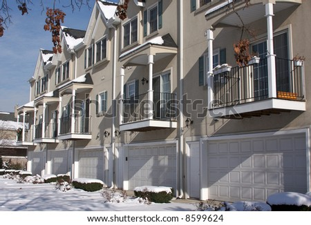 Modern Apartment Facade with Balconies and Garage Doors - stock photo