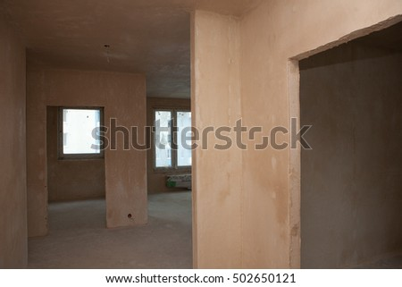 Modern apartment renovation. Plastered walls, wallpapering, painted ceiling, leveled floor. Electrical wiring installation. Empty light interior