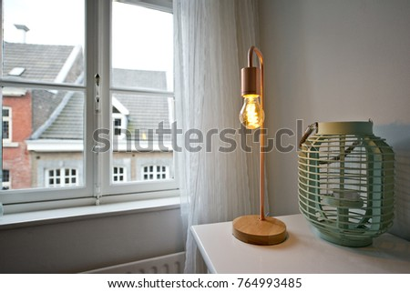 Modern apartment with a turquoise candle holder and a copper light next to the window