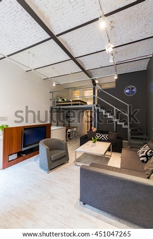 Modern apartment with stylish living room furniture set, television, stairs, mezzanine and brick roof