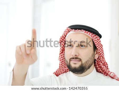 Modern arabic businessman with finger on copy space for your message