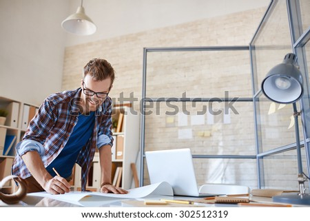 Modern architect with pencil drawing sketch of construction in office - stock photo