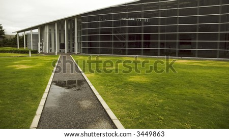 modern architecture, glass wall and straight road to hall's entrance - stock photo