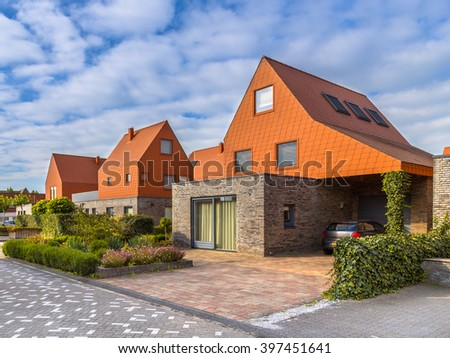 Modern architecture houses with remarkable red roof tiles in a contemporary suburban neighborhood in the Netherlands - stock photo