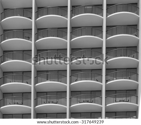 Modern architecture patios on a high rise building in tones of black, white, and gray/grey, for use as an advertisement background or for use as wallpaper. - stock photo
