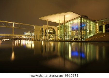 modern architecture reflecting in water - stock photo