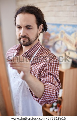 Modern artist painting in studio - stock photo