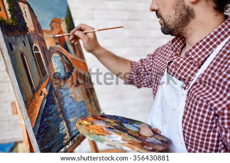 Modern artist painting landscape with oilpaints - stock photo