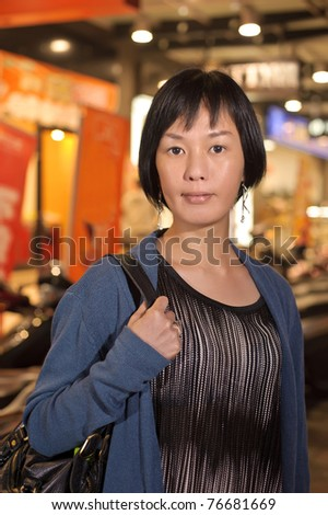 Modern Asian beauty in city night,  half length closeup portrait on dark and illuminated urban background.
