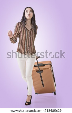 Modern Asian woman running and holding a suitcase. - stock photo