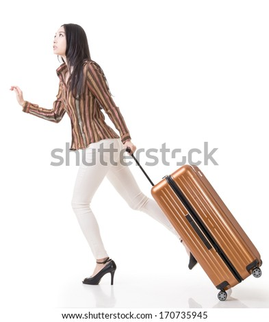 Modern Asian woman running and holding a suitcase, side view full length portrait isolated on white background. - stock photo