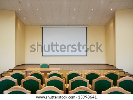 Modern auditorium hall for presentation with projection screen - stock photo
